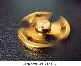 Fidget spinner on dark leather background