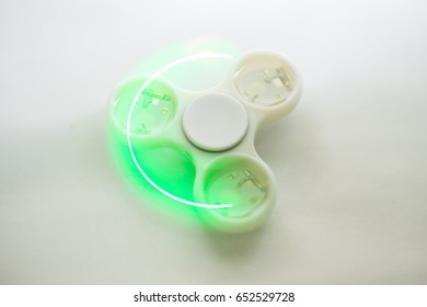 Fidget spinners with led light, stress relieving toy. Motion blur due to slow shutter speed applied