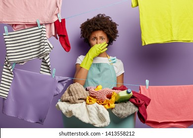 Fie, what stench! Shocked dissatisfied ethnic female housekeeper closes nose, smells dirty laundry from basket, busy with washing clothes during weekend, wears green rubber gloves and apron.