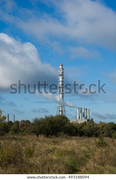 Field in autumn and industrial chimney in the background.