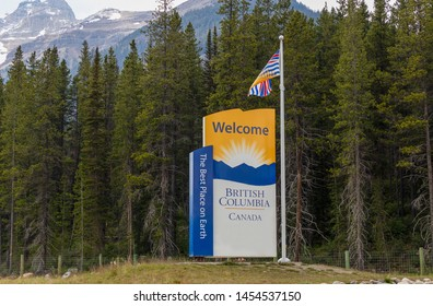 Field, BC / Canada - June 21, 2019: Welcome to British Columbia sign with pine trees and snow-capped peaks of the Rocky Mountains in the background at the border of British Columbia and Alberta.