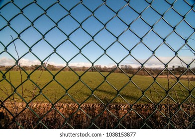 Field behind a green gate simulating a prison yard