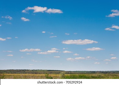 Field and blue sky background. Rural summer landscape with clear horizon and fluffy clouds