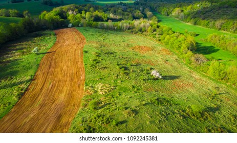 a field of cultivated land in aerial view, in the middle of green nature