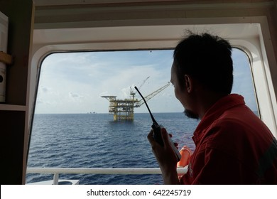 Field engineer communicate with offshore platform crew using walkie talkie.