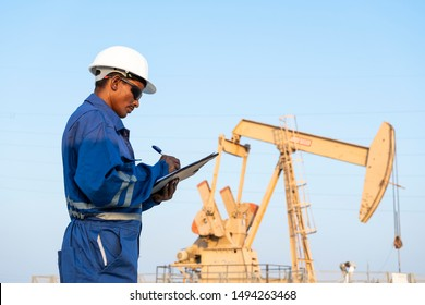 Field engineer monitoring crude oil pump in the oilfield.
