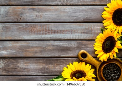 Field flowers design with sunflowers and seeds frame on wooden background top view space for text