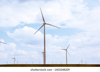 Field full with wind turbines facing different directions. Windmill against the background of the sky in a cloudy season.