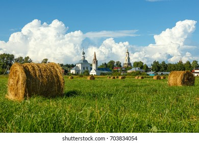 Field with haystacks and old churches in Suzdal