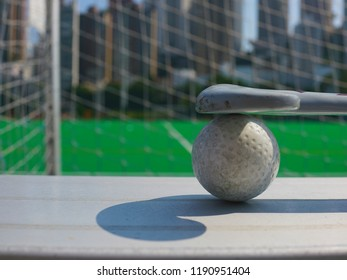 Field hockey ball and stick with astroturf and net in background