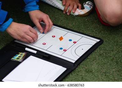 Field hockey coach hands showing some play on magnetic board