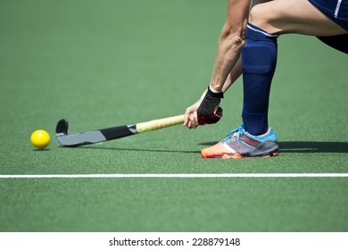 Field Hockey player, forcefully passing the ball to a tream mate