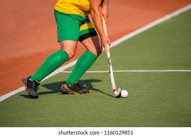 Field hockey player, in possesion of the ball, running over an astroturf pitch, looking for a team mate to pass to