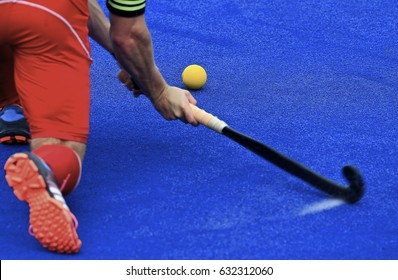Field hockey players control the ball.