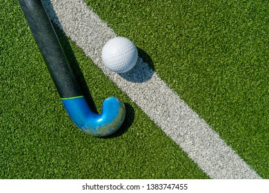 Field hockey stick and ball on the green field