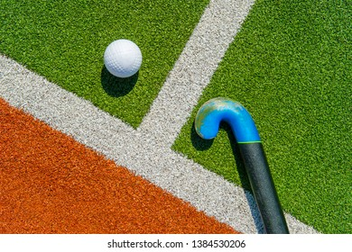 Field hockey stick and ball on brown and green grass