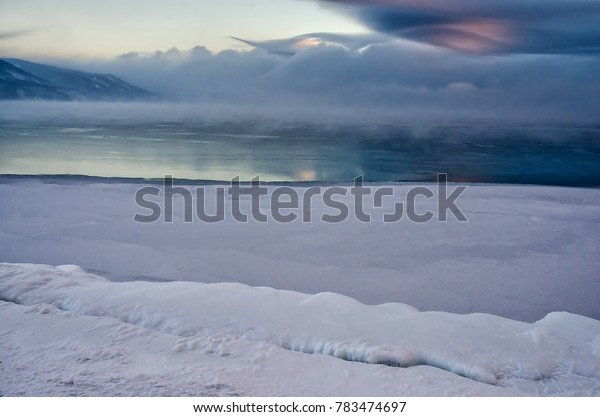 Field of ice hummocks on the frozen Lake Baikal. Sunset