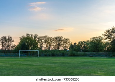 Field with net-less football goal during beautiful sunset
