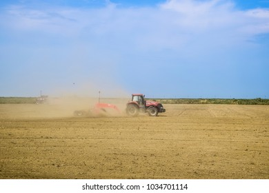 Field next to Krasnodar, Russia - August 08, 2016: A tractor with a grader aligns the soil on the field. The tractor raised dust.