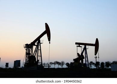 In the field, the oil pump in the evening, the evening silhouette of the pumping unit, the silhouette of the oil pump