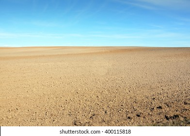 A field of plowed ground on a background of blue sky.