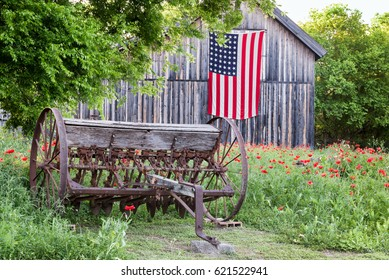 Field of red poppies with farm equipment and barn with US flag