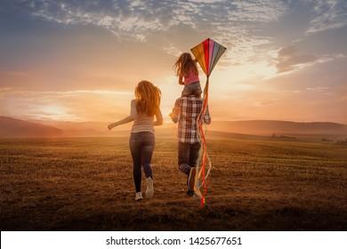 Feldlauffamilie mit Ballons und Drachen