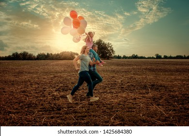 field running family with balloons and kite