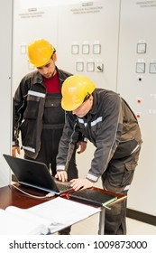 Field service crew engineers inspect relay protection system with laptop computer. Bay control unit. Medium voltage switchgear