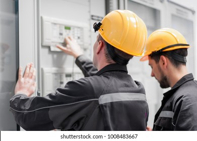 Field service crew testing electronics or inspecting electrical installation system. Bay control unit. Medium voltage switchgear