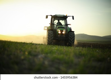 in the field, tractor harvesting. Farmer trying to finish sunset works with his tractor.