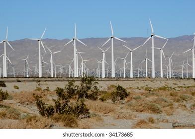 field of wind turbines in the desert against blue sky