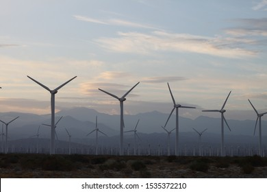 A field of windmills spin in front of a colorful sky. 4183