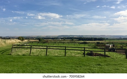 field in Yorkshire. Countryside view with fenced area, farmland. Blue sky with some cloud.