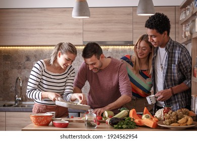 Fiends preparing vegetarian meal.They preparing food and making fun in the kitchen.Home party.
