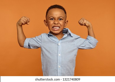 Fierce angry emotional dark skinned male expressing fury or rage keeping fists and teeth clenched, being mad with bully, ready to punch him back. Negative human facial expressions and reaction