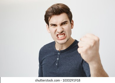 Fierce confident stylish european dark-haired male with trendy haircut holding fist in front of him as if ready for fight or challenge, clenching white teeth, having aggressive expression on face