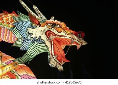 Fierce dragon face paper sculpture shining in the dark at a Asian lantern festival.