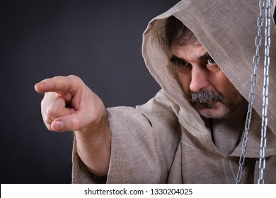 A fierce monk-man with a beard is pointing somewhere.