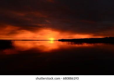 Fiery horizon line at sunset on the lake