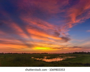 A fiery orange sunset sky over rural Thailand