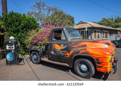 A fiery painted old timey truck next to an even older gas pump in a little town on Kauai, Hawaii