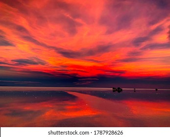 Fiery red purple sunset over salt marsh in Salar de Uyuni,Bolivia. Stunning sunset sky.The Mars-like landscape of the world's largest salt flat. Surreal beautiful view evening playa Tunupa. Reflection