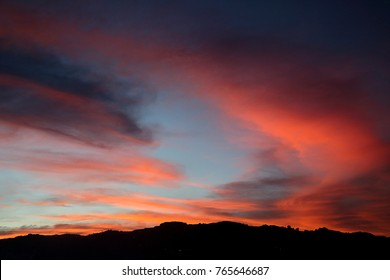 A fiery red sunset with red-orange band of clouds against a blue background and a silhouette of the mountain at the foreground.