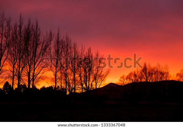 Fiery sky over the Blue Mountains in Tapanui, New Zealand.