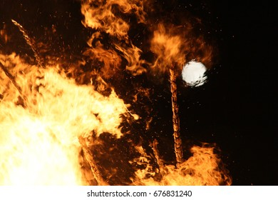 Fiery Solstice Fire In The middle of june, where the days from there on get shorter again with burning wooden sticks, orange flames and the full moon in the dark background