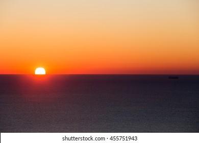 fiery sun rises over the sea