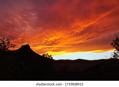 A fiery sunset creates dramatic colors over the silhouette of Thumb Butte.