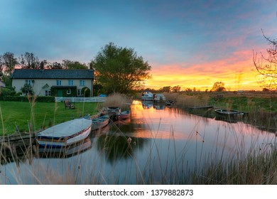 Fiery sunset over boats moored on the river at West Somerton a picturesque village on the Norfolk Broads