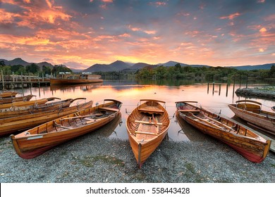 A fiery sunset over boats on the shore of Derwentwater at Keswick in the Lake District in Cumbria